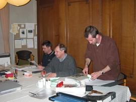 Inplakken krantenknipsels dijkverzwaring door werkgroepleden